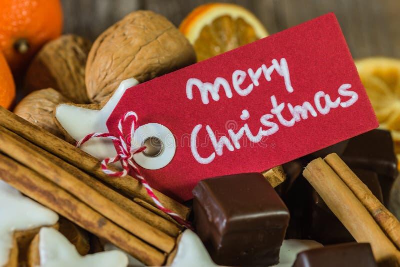 Μπισκότα, σοκολάτες, καρύδια, πορτοκάλια και κανέλα Χριστουγέννων με τη Χαρούμενα Χριστούγεννα ευχετήριων καρτών στοκ φωτογραφία
