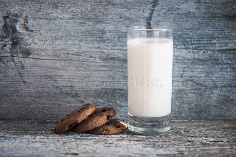 Μπισκότα τσιπ σοκολάτας, γάλα, αγροτικό ξύλινο υπόβαθρο στοκ φωτογραφία
