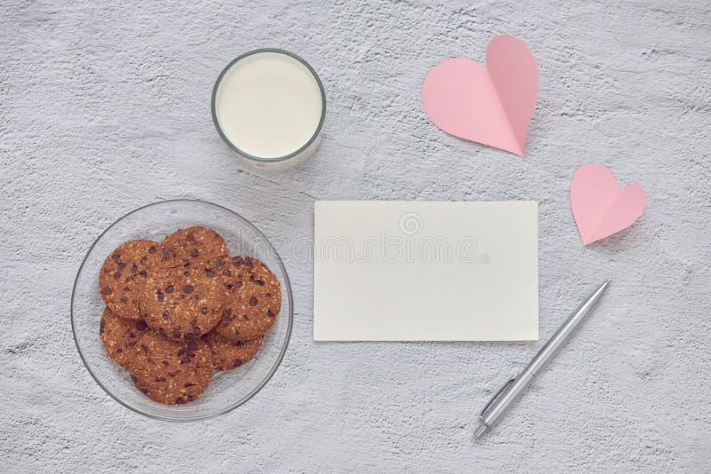 Μπισκότα τσιπ σοκολάτας στο πιάτο και το ποτήρι του καφέ γάλακτος με την κάρτα μηνυμάτων αγάπης στο άσπρο υπόβαθρο πετρών στοκ εικόνες