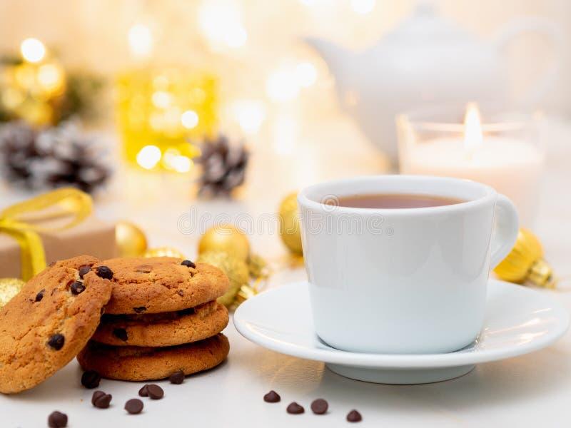 Μπισκότα τσιπ σοκολάτας, φλυτζάνι του τσαγιού στο ελαφρύ υπόβαθρο Χριστουγέννων στοκ εικόνα