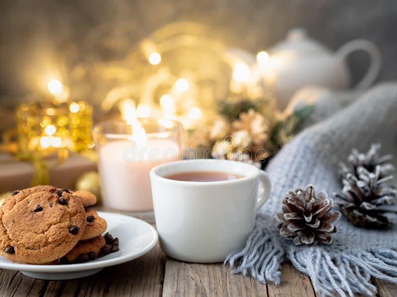 Μπισκότα τσιπ σοκολάτας, φλυτζάνι του τσαγιού στο σκοτεινό υπόβαθρο Χριστουγέννων στοκ φωτογραφίες