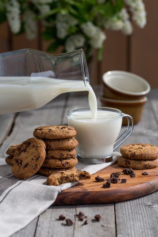 Μπισκότα τσιπ σοκολάτας με το γάλα στον παλαιό αγροτικό ξύλινο πίνακα στοκ εικόνα