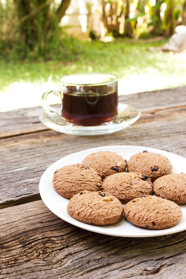 Μπισκότα τσιπ σοκολάτας στο άσπρο πιάτο με ένα ποτήρι του καφέ στοκ εικόνα