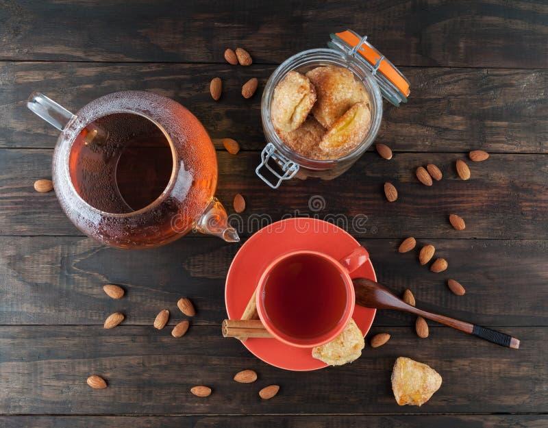 Μπισκότα τυριών εξοχικών σπιτιών σε ένα βάζο και ένα μαύρο τσάι στοκ εικόνα