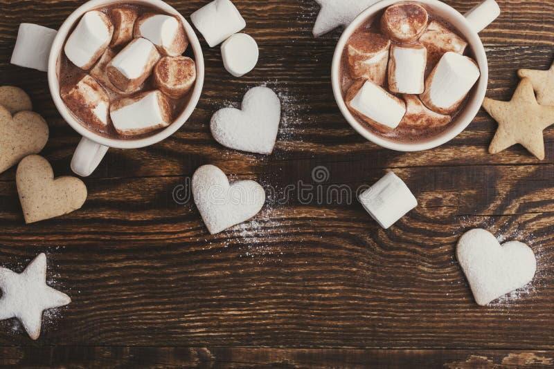 Μπισκότα Χριστουγέννων που ψεκάζονται με την κονιοποιημένα ζάχαρη και τα φλυτζάνια της καυτής σοκολάτας με marshmallows στον ξύλι στοκ φωτογραφία
