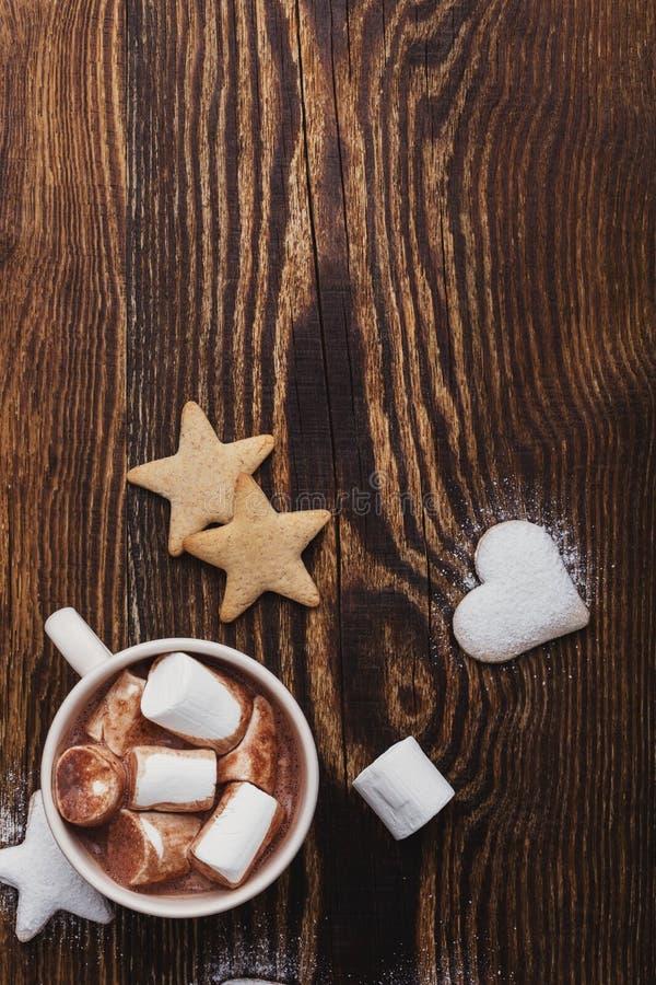 Μπισκότα Χριστουγέννων που ψεκάζονται με την κονιοποιημένα ζάχαρη και το φλυτζάνι της καυτής σοκολάτας με marshmallows στον ξύλιν στοκ εικόνα με δικαίωμα ελεύθερης χρήσης
