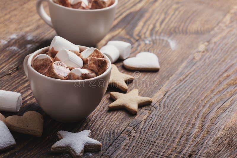 Μπισκότα Χριστουγέννων που ψεκάζονται με την κονιοποιημένα ζάχαρη και τα φλυτζάνια της καυτής σοκολάτας με marshmallows στοκ φωτογραφία με δικαίωμα ελεύθερης χρήσης