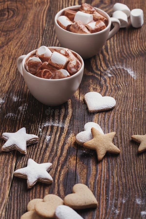 Μπισκότα Χριστουγέννων που ψεκάζονται με την κονιοποιημένα ζάχαρη και τα φλυτζάνια της καυτής σοκολάτας με marshmallows στοκ φωτογραφίες