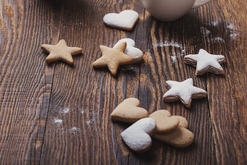 Μπισκότα Χριστουγέννων που ψεκάζονται με την κονιοποιημένα ζάχαρη και τα φλυτζάνια της καυτής σοκολάτας με marshmallows στοκ εικόνα