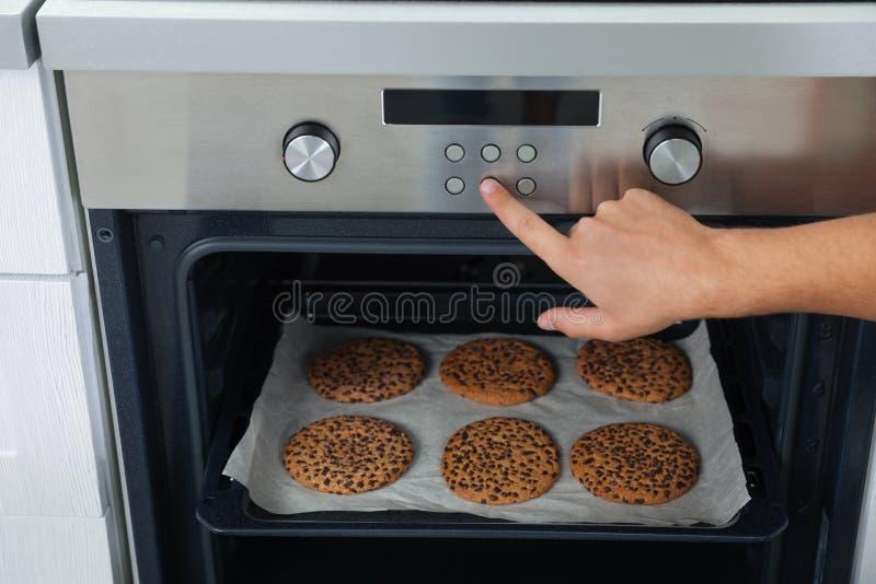 Μπισκότα ψησίματος νεαρών άνδρων στο φούρνο στο σπίτι στοκ φωτογραφίες με δικαίωμα ελεύθερης χρήσης