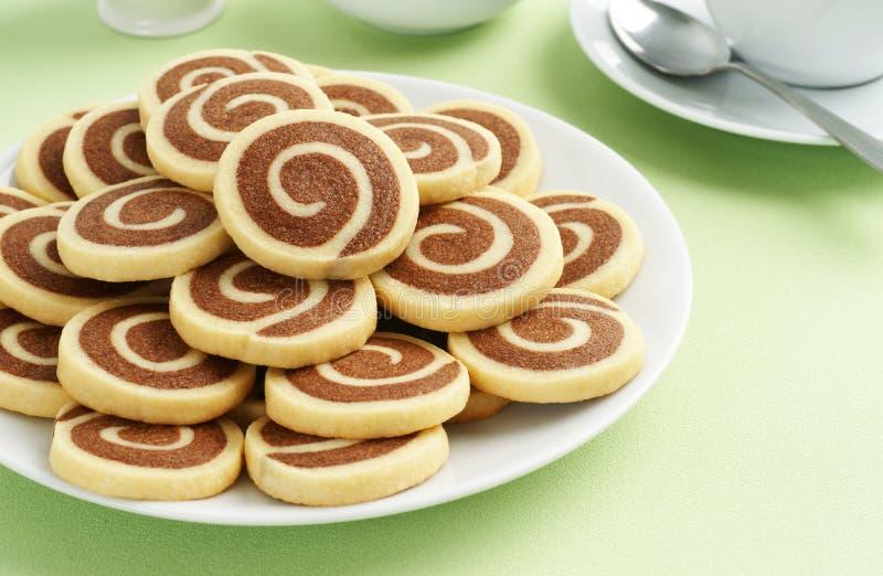 Μπισκότα Pinwheel σοκολάτας και βανίλιας με το τσάι στοκ φωτογραφίες