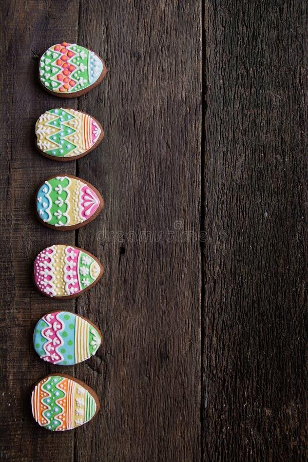 Μπισκότο μελοψωμάτων υπό μορφή αυγών χρώματος στο σκοτεινό ξύλινο υπόβαθρο στοκ εικόνα με δικαίωμα ελεύθερης χρήσης