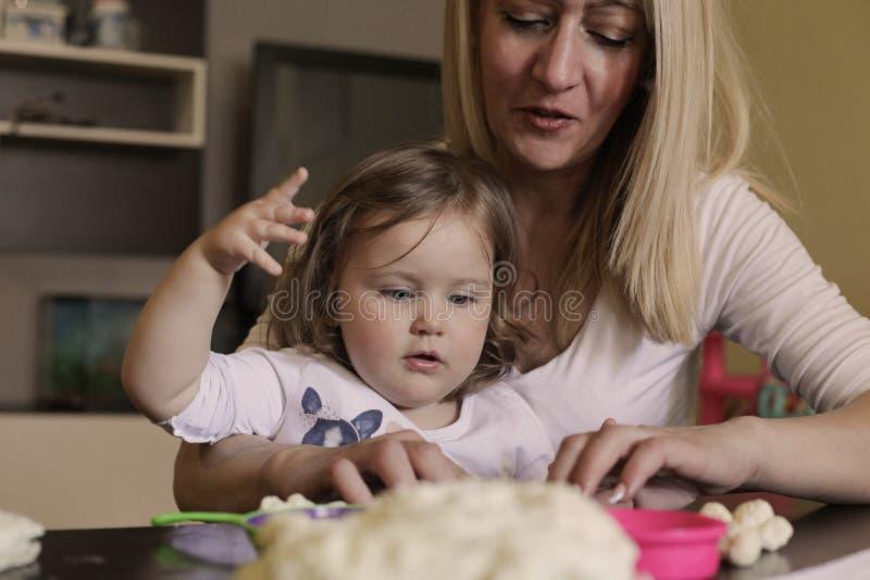 Μπισκότο ψησίματος μητέρων και κοριτσιών χαμόγελου από κοινού στοκ εικόνες