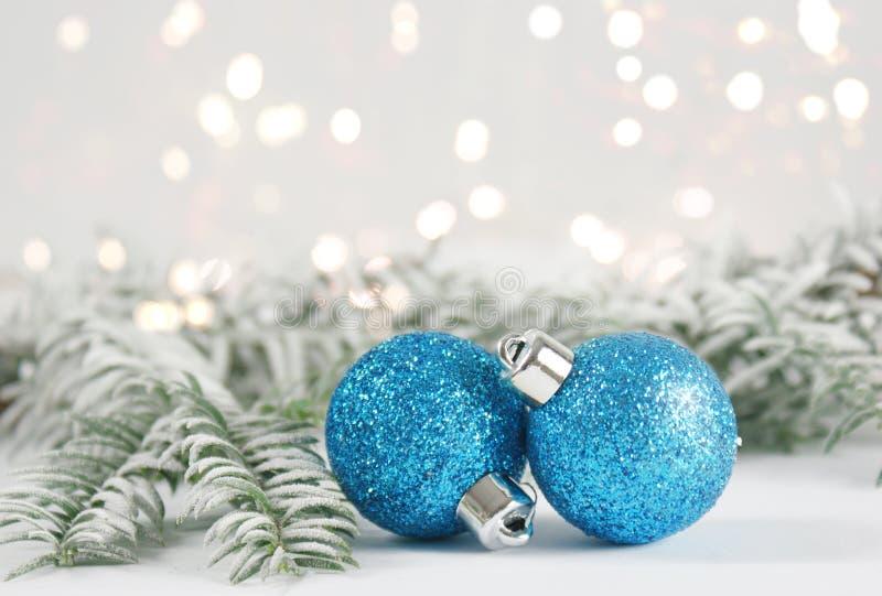 Μπιχλιμπίδια Χριστουγέννων με τους χιονώδεις κλάδους δέντρων έλατου στοκ εικόνα