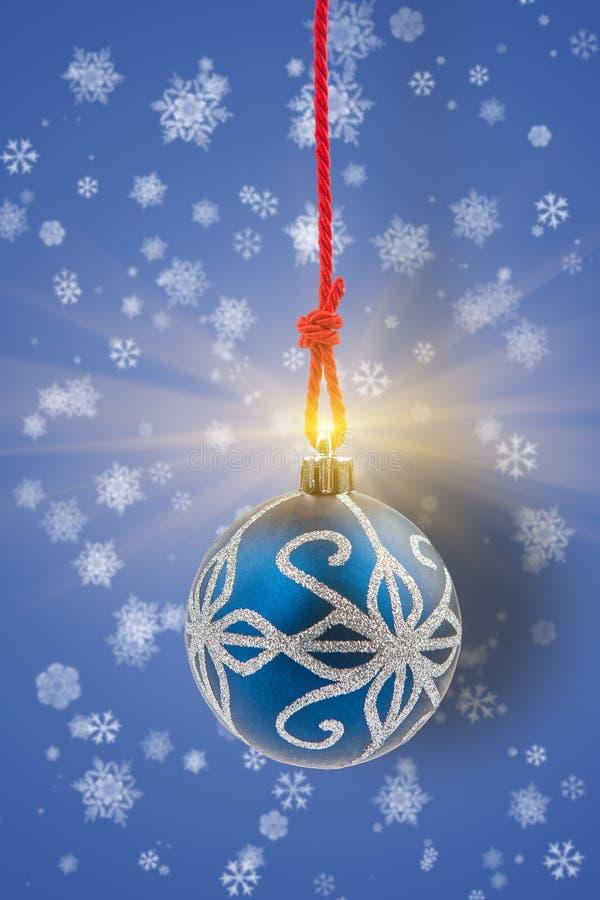 Μπιχλιμπίδι Χριστουγέννων με να λάμψει το φως στο υπόβαθρο με snowflake στοκ εικόνες