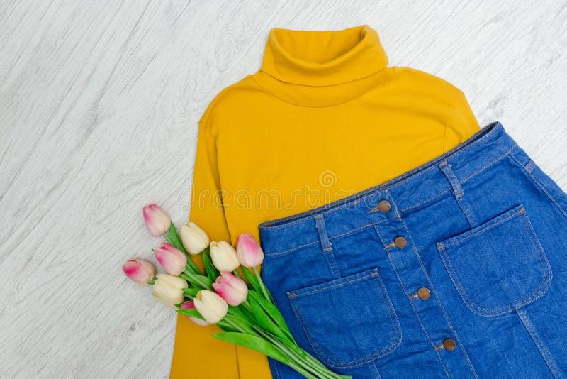 μπλε έξυπνη γυναίκα μόδας προσώπου έννοιας ομορφιάς makeup Κίτρινο turtleneck, μπλε φούστα και ρόδινες τουλίπες στοκ εικόνες