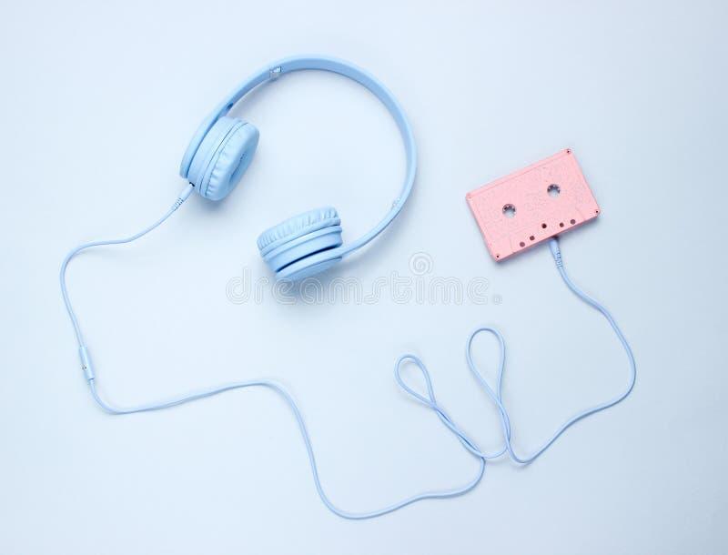 Μπλε ακουστικά με το καλώδιο στην ακουστική κασέτα στοκ εικόνες