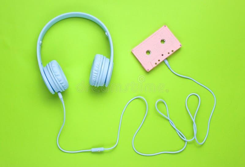 Μπλε ακουστικά με το καλώδιο στην ακουστική κασέτα στο πράσινο υπόβαθρο στοκ εικόνες