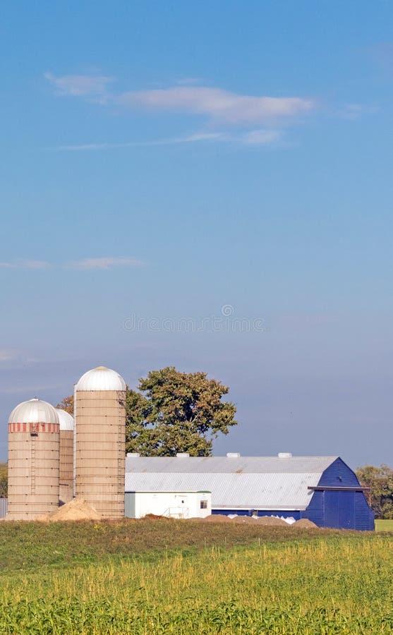 Μπλε αχυρώνας και τρία σιλό, μπλε ουρανός και λευκά σύννεφα στοκ φωτογραφίες