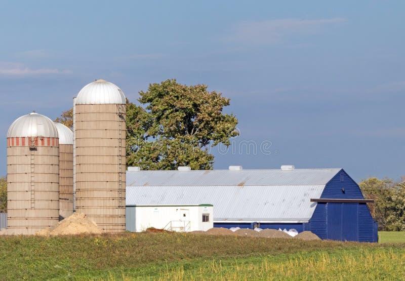 Μπλε αχυρώνας και τρία σιλό, μπλε ουρανός και λευκά σύννεφα στοκ φωτογραφία με δικαίωμα ελεύθερης χρήσης
