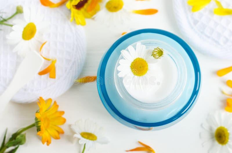 Μπλε βάζο γυαλιού Ligh με την άσπρες του προσώπου κρέμα/τη μάσκα Ð ¡ hamomile και λουλούδια calendula στο άσπρο υπόβαθρο στοκ εικόνες με δικαίωμα ελεύθερης χρήσης