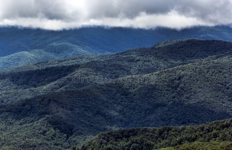 Μπλε βουνά κορυφογραμμών και πουπουλένια σύννεφα στο φυσώντας βράχο στοκ φωτογραφία με δικαίωμα ελεύθερης χρήσης
