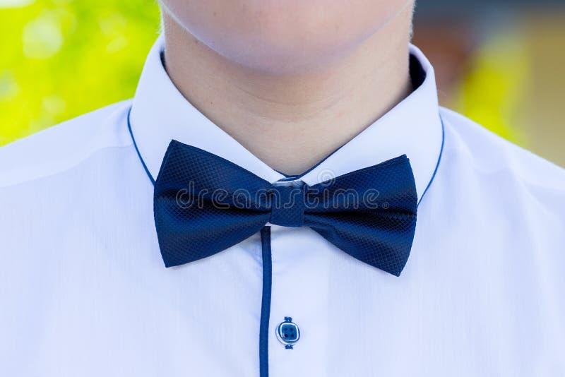 Μπλε δεσμός τόξων σε ένα άσπρο πουκάμισο ενός νέου man_ στοκ φωτογραφία με δικαίωμα ελεύθερης χρήσης