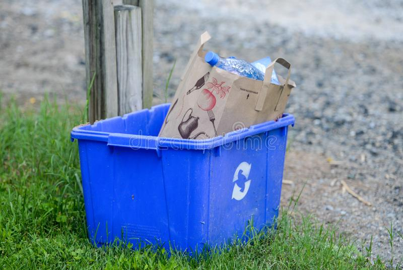 Μπλε δοχείο ανακύκλωσης που γεμίζουν με το έγγραφο στοκ εικόνα