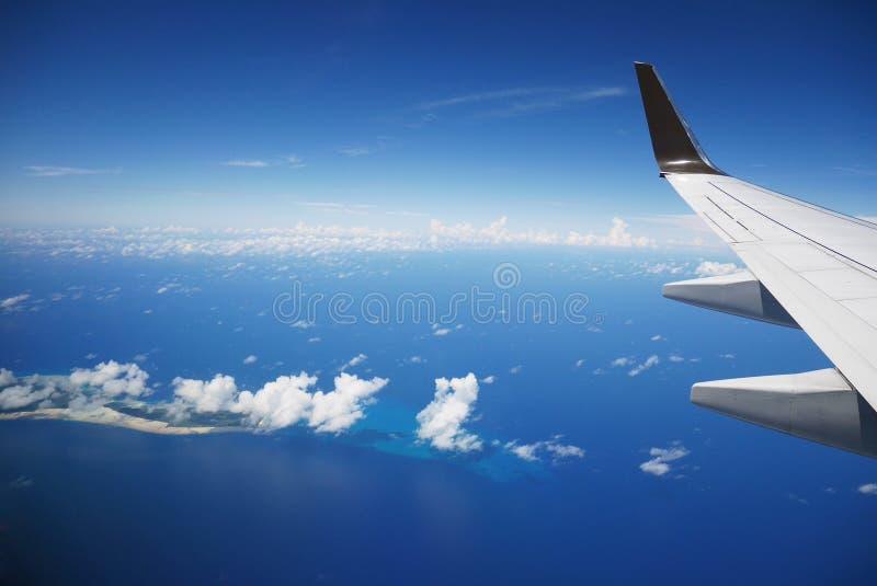 Μπλε Ειρηνικός Ωκεανός, σύννεφα και ουρανός την ηλιόλουστη ημέρα μέσω του παραθύρου αεροπλάνων στοκ φωτογραφία