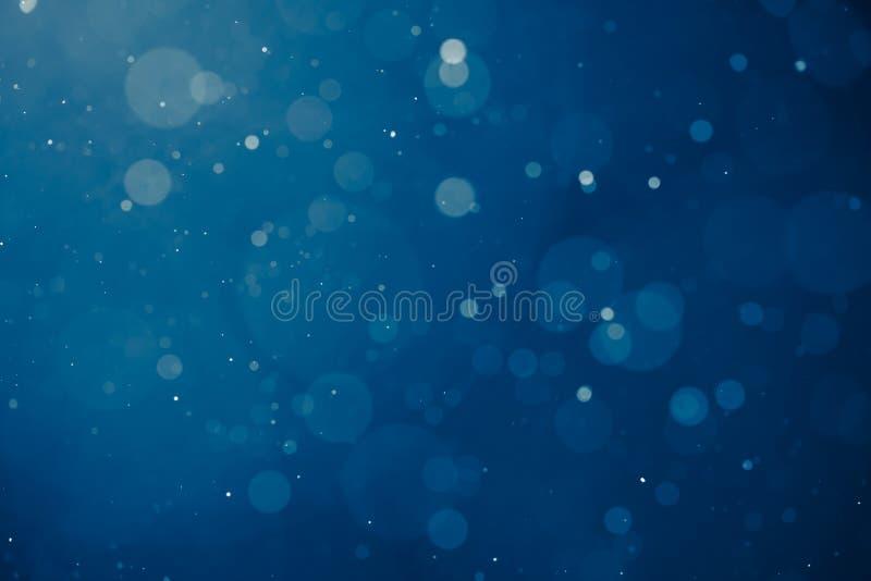 Μπλε ελαφρύ υπόβαθρο με snowflakes τα μόρια στοκ εικόνες