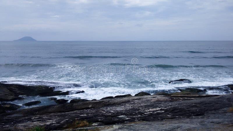 Μπλε θάλασσα με τα κύματα και τους βράχους στοκ φωτογραφία