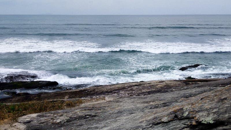 Μπλε θάλασσα με τα κύματα και τους βράχους στοκ εικόνα