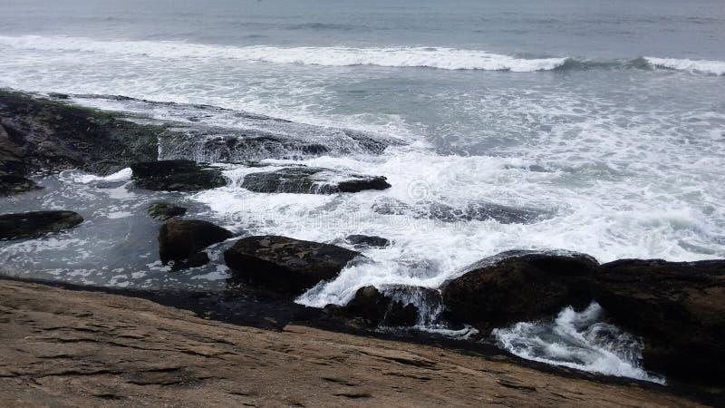 Μπλε θάλασσα με τα κύματα και τους βράχους στοκ εικόνες