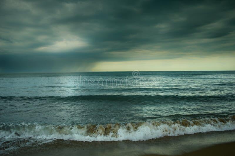 Μπλε θάλασσα με τα μαύρα σύννεφα στοκ εικόνες