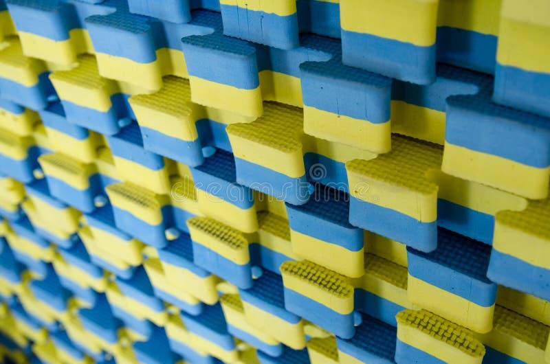 Μπλε-κίτρινα αθλητικά χαλιά που συσσωρεύονται στο μεγάλο σωρό στοκ εικόνες με δικαίωμα ελεύθερης χρήσης