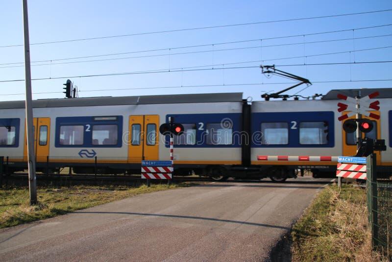 Μπλε κίτρινο άσπρο τραίνο sprinter σε έναν σιδηρόδρομο που διασχίζει σε Moordrecht στοκ φωτογραφίες