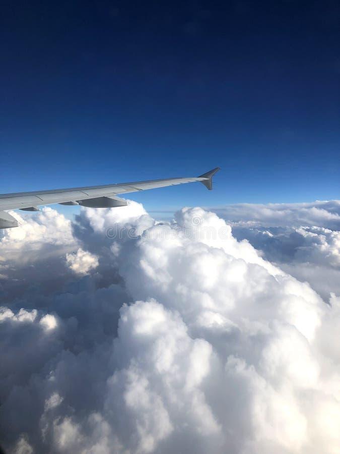 Μπλε και άσπρα σύννεφα Χιλιάδες χιλιόμετρα επάνω από τη γη Καμπίνα αεροπλάνων ή αεροσκαφών Κλείστε τα φω'τα κατά τη διάρκεια της  στοκ εικόνες
