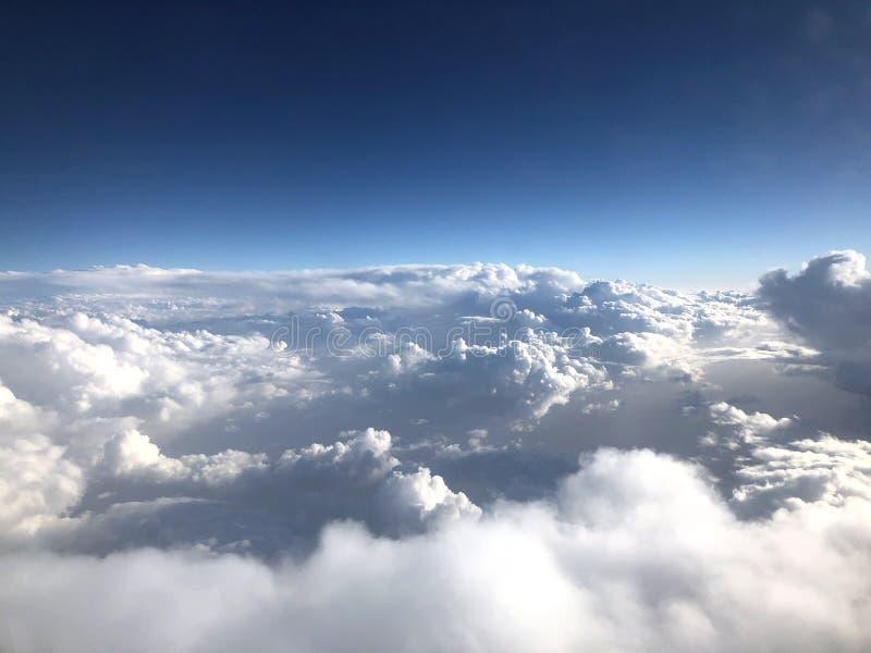 Μπλε και άσπρα σύννεφα Χιλιάδες χιλιόμετρα επάνω από τη γη Καμπίνα αεροπλάνων ή αεροσκαφών Κλείστε τα φω'τα κατά τη διάρκεια της  στοκ φωτογραφία