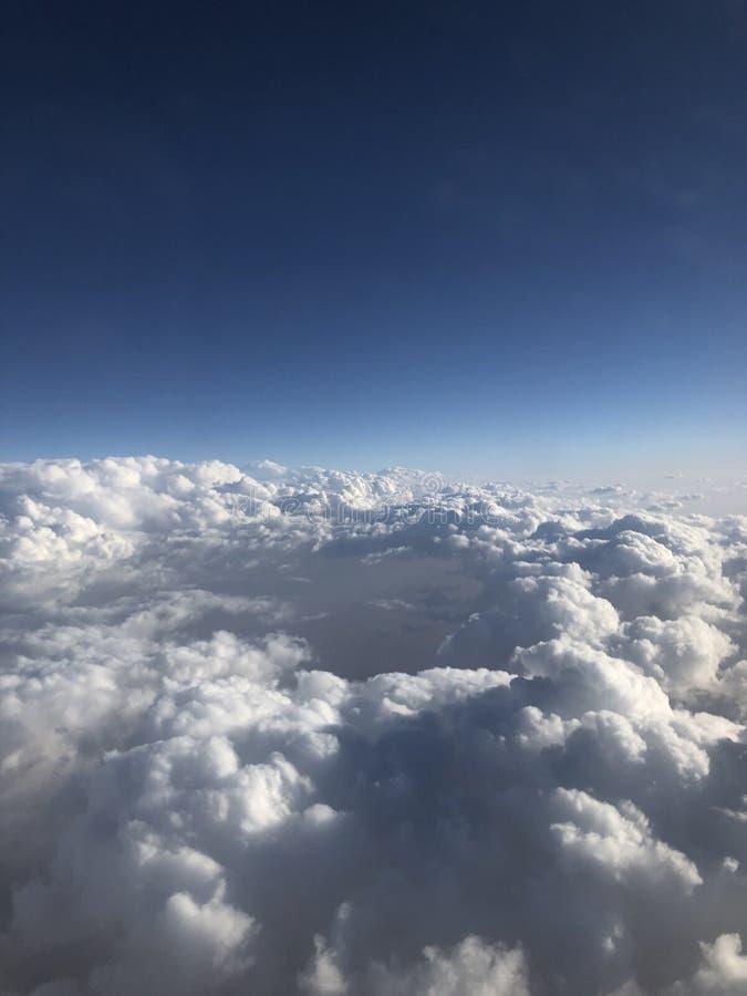 Μπλε και άσπρα σύννεφα Χιλιάδες χιλιόμετρα επάνω από τη γη Καμπίνα αεροπλάνων ή αεροσκαφών Κλείστε τα φω'τα κατά τη διάρκεια της  στοκ φωτογραφίες