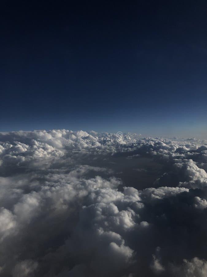 Μπλε και άσπρα σύννεφα Χιλιάδες χιλιόμετρα επάνω από τη γη Καμπίνα αεροπλάνων ή αεροσκαφών Κλείστε τα φω'τα κατά τη διάρκεια της  στοκ εικόνα