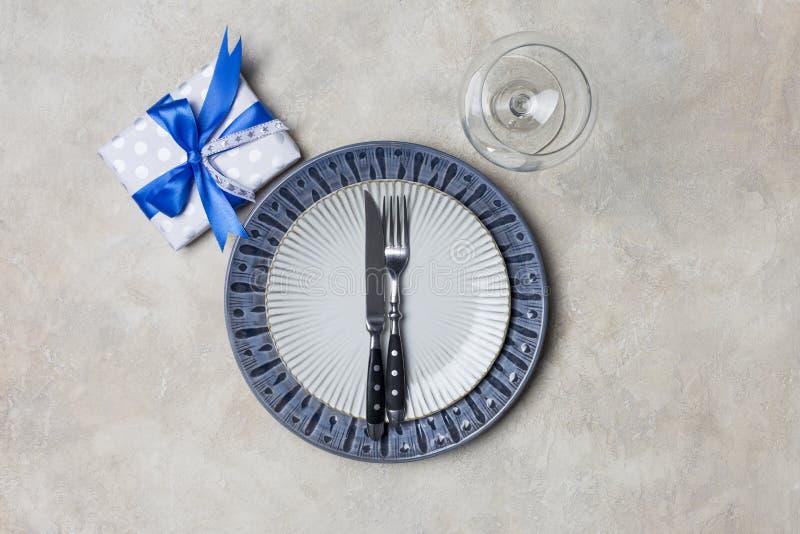 Μπλε και άσπρο πιάτο πιάτων με το παρόν κιβώτιο για τα άτομα με το δίκρανο και το μαχαίρι, γυαλί κρασιού στο άσπρο υπόβαθρο στοκ εικόνα με δικαίωμα ελεύθερης χρήσης