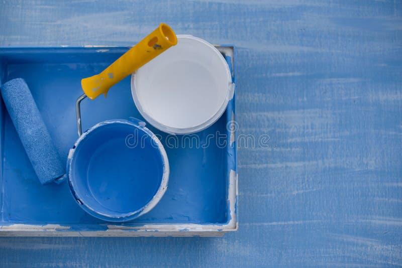 Μπλε και άσπρο χρώμα κατά τη τοπ άποψη δοχείων κύλινδρος με μια κίτρινη λαβή για τη ζωγραφική των τοίχων στοκ φωτογραφία με δικαίωμα ελεύθερης χρήσης