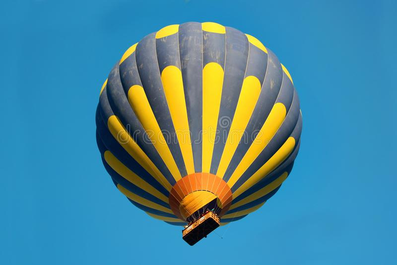 Μπλε και κίτρινο ριγωτό μπαλόνι στον ουρανό στοκ εικόνες