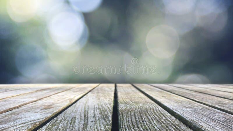 Μπλε και πράσινα φω'τα Bokeh με την ξύλινη επιτραπέζια κορυφή στοκ φωτογραφίες