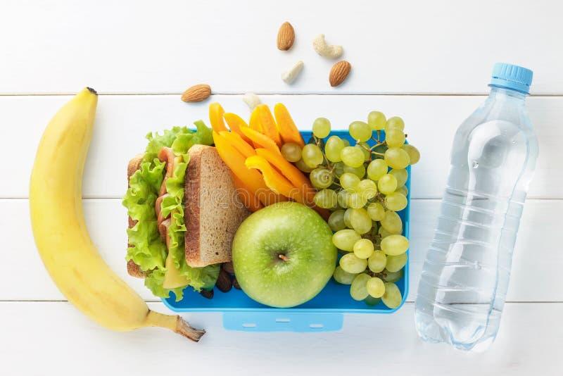 Μπλε καλαθάκι με φαγητό με τα υγιή τρόφιμα για τα παιδιά σχολείου με το μπουκάλι νερό στο άσπρο ξύλινο υπόβαθρο στοκ εικόνα με δικαίωμα ελεύθερης χρήσης