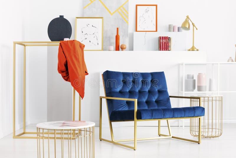 Μπλε καναπές βενζίνης στη μέση του μοντέρνου άσπρου καθιστικού με τα χρυσά εξαρτήματα και το μέρος της τέχνης στοκ εικόνες