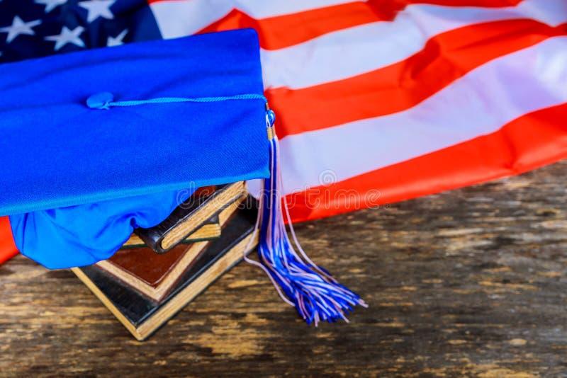 μπλε καπέλο βαθμολόγησης στα βιβλία με το υπόβαθρο αμερικανικών σημαιών στοκ φωτογραφία