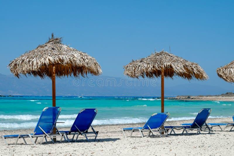 Μπλε καρέκλες γεφυρών που αγνοούν τον τροπικό, τυρκουάζ ωκεανό κάτω από μια ομπρέλα αχύρου στην άσπρη αμμώδη παραλία στοκ φωτογραφίες με δικαίωμα ελεύθερης χρήσης