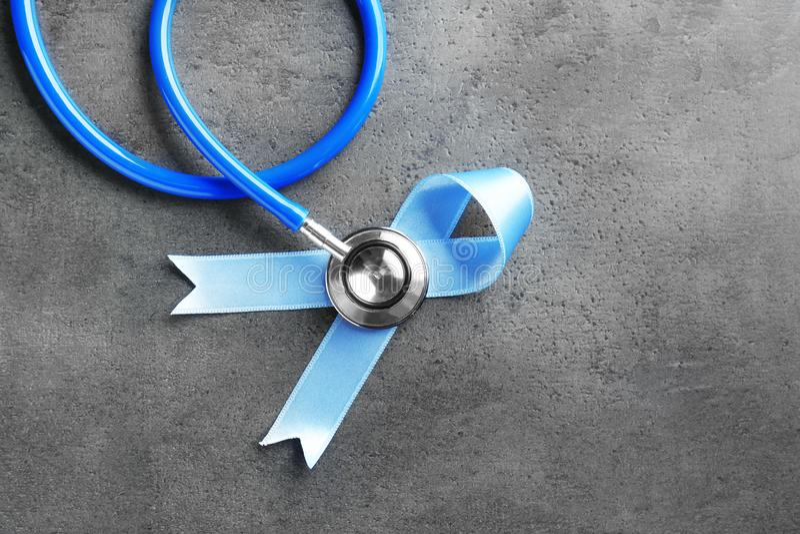 Μπλε κορδέλλα και στηθοσκόπιο στο γκρίζο υπόβαθρο στοκ φωτογραφία