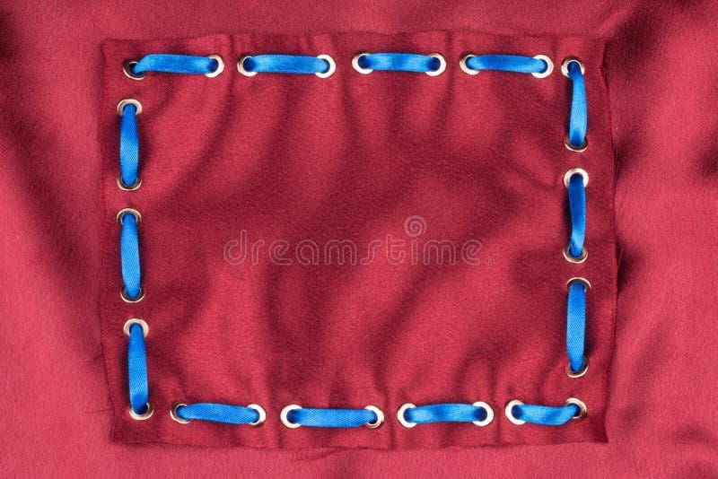 Μπλε κορδέλλα μεταξιού που παρεμβάλλεται στα χρυσά δαχτυλίδια Μοντέρνο υπόβαθρο E στοκ φωτογραφία